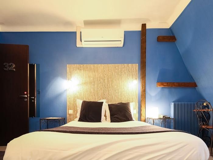 chambre lit double, tête de lit aspect bois tissé mur bleu